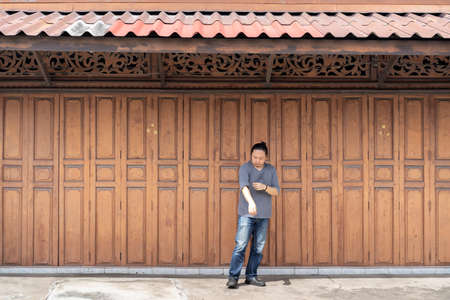 Asian long hair man is standing and posting in front of Classic backdrop wood wall and door in front of Thailand vintage traditional Building.