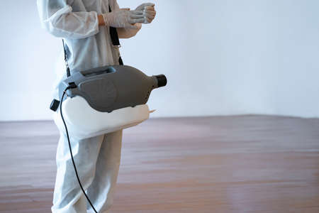 Professional technical man in prevention suit sprays sterilizing solutionby electrical prepares himself before spray machine on the wood floor and white background with studio light.
