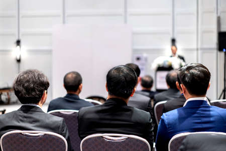 Backside of three Asian business men sit and listended speaker on the podium in front of the conference room.