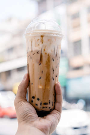 bubble ball ice Milk Tea in the hand with blur Asia building background.
