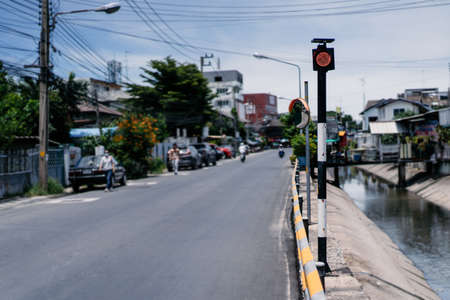 The traffice light pole with only red light on it between canal and road in the local road at Chonburi Province (East of Thailand). 免版税图像