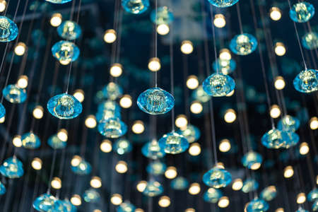 The Wallpaper Turquoise yellow light Crystal Mobile and bokeh light are hanged on the ceiling. 免版税图像