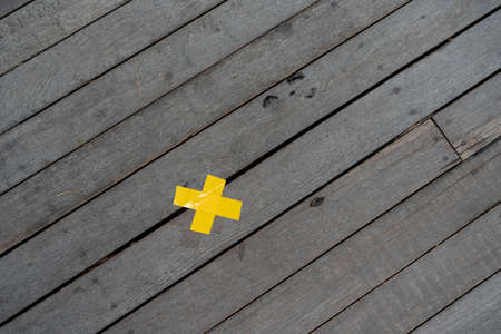 yellow cross marking tape on the wood board floor from top view shooting at outdoor field for background or backdrop