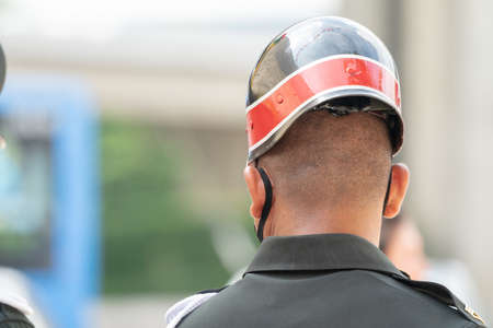 Asian Soldier in backside uniform stands to observation and watch for protection all around the event area.