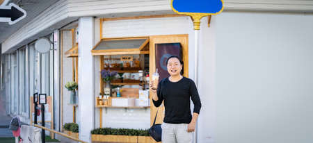Asian man in the black t-shirt holds the bubble ball ice Milk Tea in front of the shop on the outdoor street footpath.