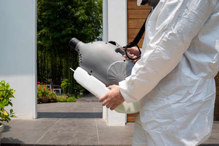 Professional technical man in prevention suit with his sterilizing machine and disinfecting water sprays in the outdoor field for purifying
