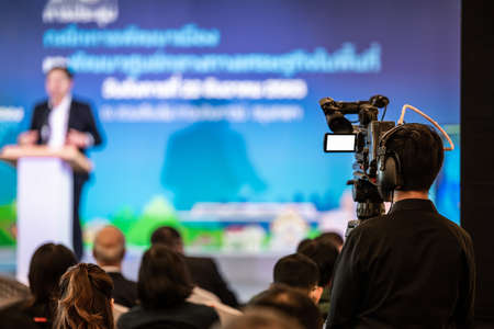 Asian man Videographer in backside are shooing and recording video in Speech event on the stage.