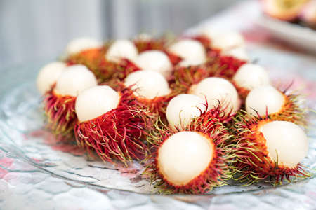 Rambutan bark is cut in half on glass dish and ready to eat.