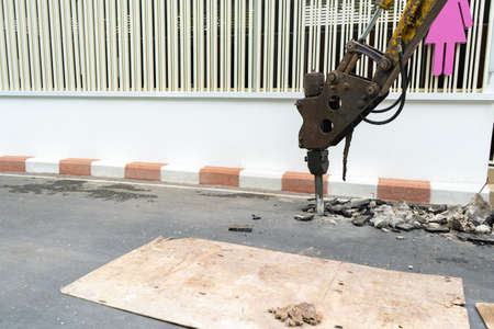Pneumatic drill demolish machine Backhoe is dicking concrete road beside the wall.