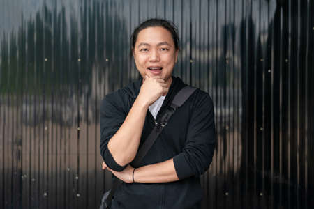 Asian man stands in front of black Zince background with the confident mood.