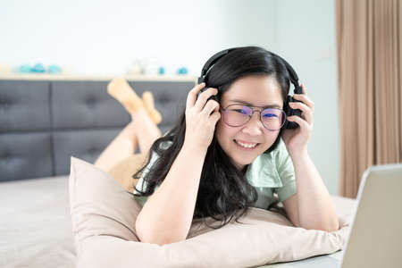 Beautiful Asian woman is using a headset with laptop and lying on the bed in her bedroom with a pastel green - brown color theme. 版權商用圖片