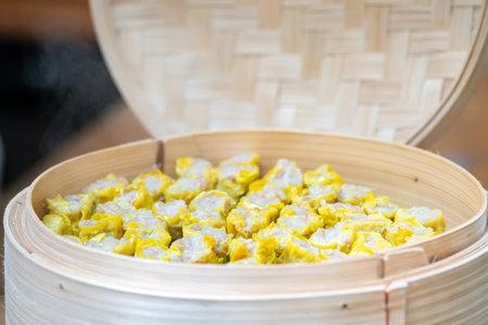 Dim Sim (Kanom jeeb) the chinese steamed dumpling on banana leaf in bamboo wicker plate for appetizer of seminar. 版權商用圖片