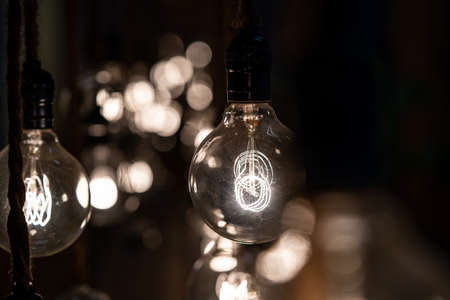 Close up to a group of hanging classic Tungsten Lamp in the dark area with rope. 版權商用圖片
