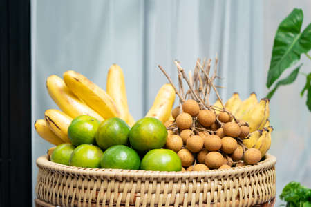 Asia Orange Banana and Longan in the basket at outdoor field, ready to eat.