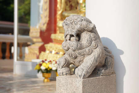 Asian white stone lion statue Chinese vintage style in front of temple on the blur background.