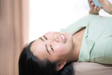 Beautiful Asian woman is lying down and playing mobile on the bed in her bedroom with a pastel green - brown color theme.