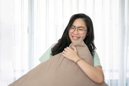Glasses beautiful Asian woman is hugging her pillow and smiling to the camera in the bedroom with a pastel green - brown color theme.