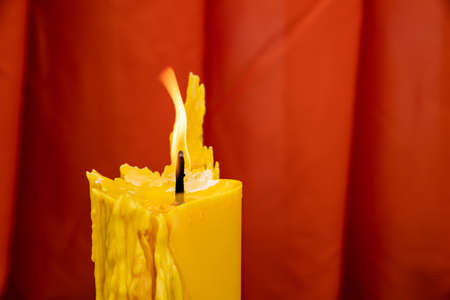 Close up to the melt yellow candle and fire flame with the red curtain background.