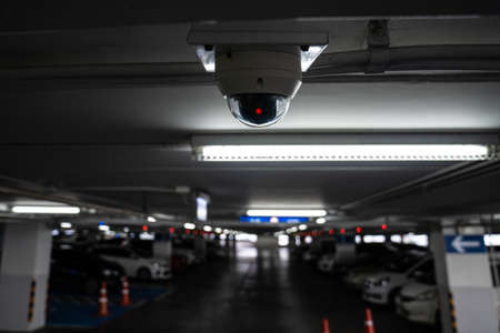 CCTV camera is installed on the car parking, ceiling for monitor and safety system control in dark low light atmosphere.