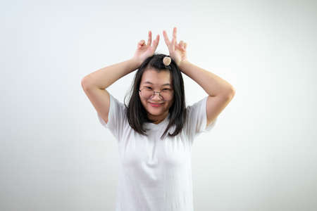 Asian glasses young woman is raising up victory sign by two fingers like the rabbit ears on white background. 版權商用圖片