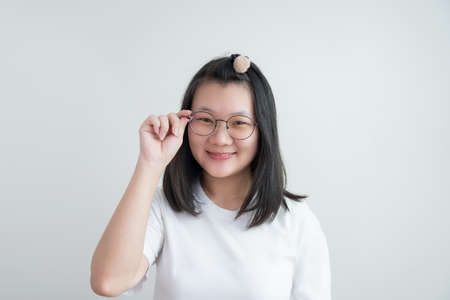 Young Asian glasses girl touches her glasses and smiles to camera on studio light white clear background. Clipping Path.