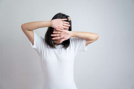 Young Asian glasses girl rises up her arms to cover her face in studio light white clear background.