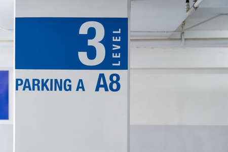 Signage on the indoor carparking pole, tell driver which way to go and location in parking lot.