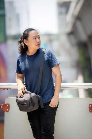 Asian long hair man looks at beside of his posing at outdoor environment. 版權商用圖片