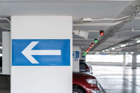 white arrow Signage on the indoor carparking pole, tell driver which way to go and location in parking lot. 版權商用圖片