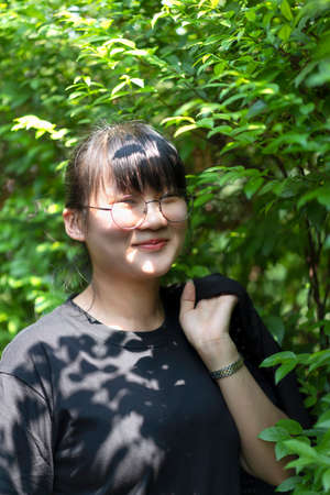 Portrait of the Asian glassese Thai woman is standing in the garden in the morning. 版權商用圖片