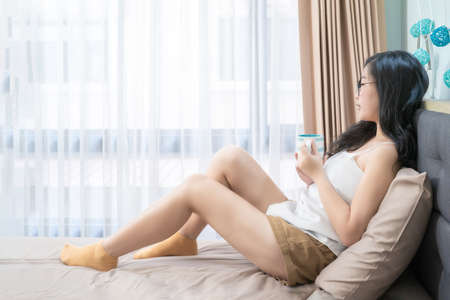 Asian Glasses Woman holds a cup of coffee and relax on the bed in the morning at her bedroom.