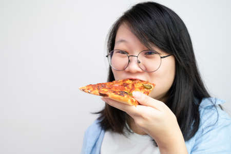 Happy glasses Asian young woman eat Pizza on white background.