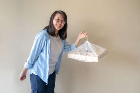 Asian glasses woman holds and hangs the paper pizza box with plastic bag with happiness for her lunch.