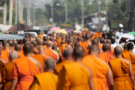 a group of monk on pilgrimage walk on the street at noon time, Thailand.
