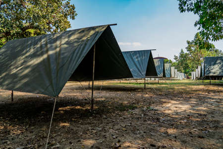 The simple and normal empty Canvas Tents in the row and column on the grass field at outdoor field in afternoon time. 版權商用圖片