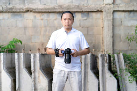 Asian man serious looks at the camera while holds th mirrorless camera medium format in the hand on the construction concret wall background.