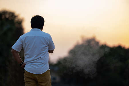 Asian man is smoking backside in the twilight time.