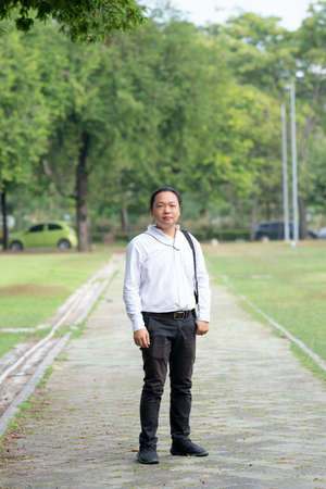Asian freelance long hair man standing and posting on the walk way in the garden outdoor field with his camera beside him. 版權商用圖片