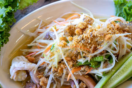 Somtum, Papaya spicy salad on white dish, the famous Thai traditional food.