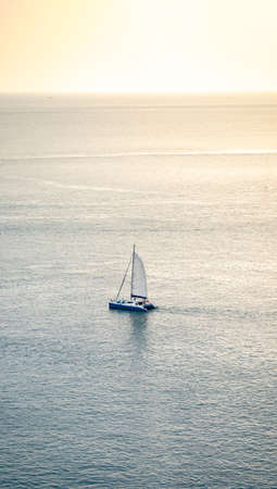 minimal Sailboat Yacht is saling on the calm sea, shoot this image from above of the mountain Phrom Thep Cape, Phuket Thailand with Tele lens.