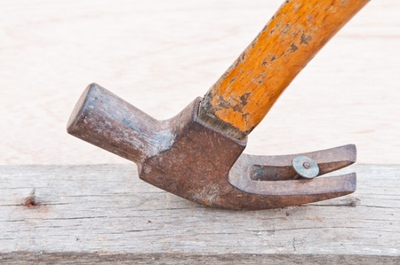 old rusted hammer pulling out a nail out of a piece Stock Photo