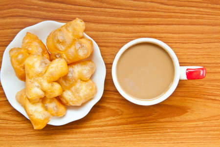fried dough and coffee on wood background