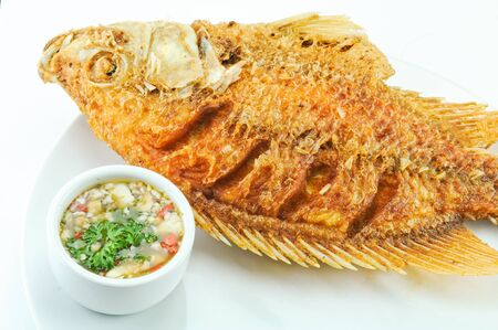 Fried red tilapia fish with spicy sauce photo