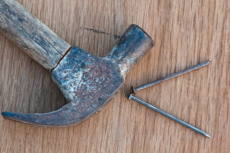 old hammer with nail on wood background Stock Photo