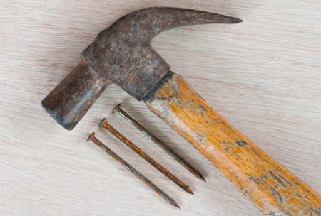 old hammer with nail on wood background photo