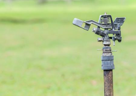 water sprinkler: metal automatic water sprinkler in the garden Stock Photo