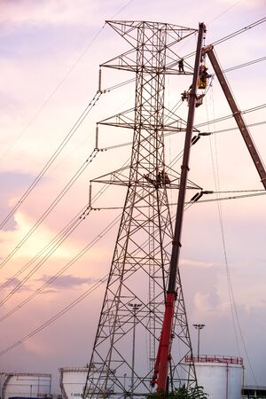 Technicians working on  electricity pole under light of  evening.