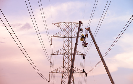 risky business: Technicians working on  electricity pole under light of  evening.