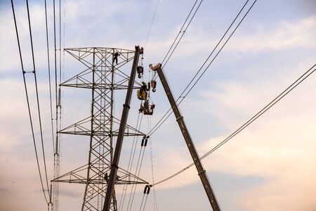 electricity pole: Technicians working on  electricity pole under light of  evening.