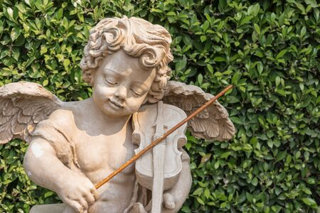cupid play music statue on green leaf background in park